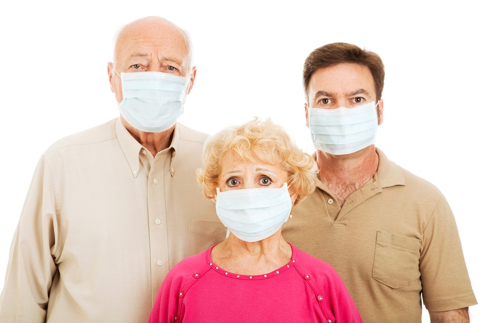 Elderly parents and their adult son wearing face masks to protect against a health care pandemic