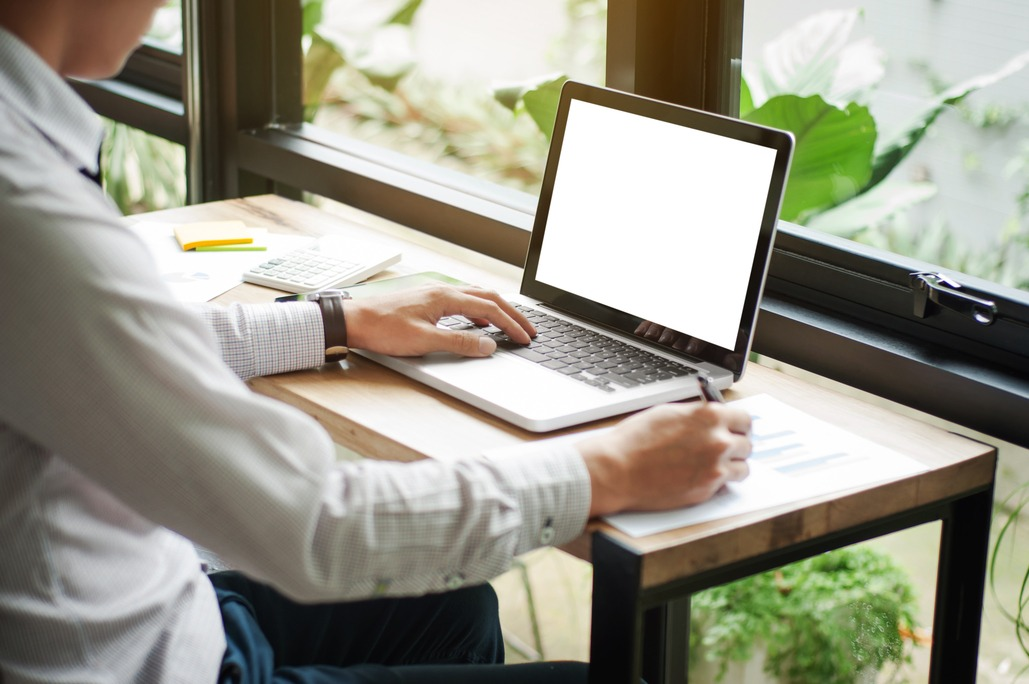 business executive using laptop with blank screen copy space at cafe