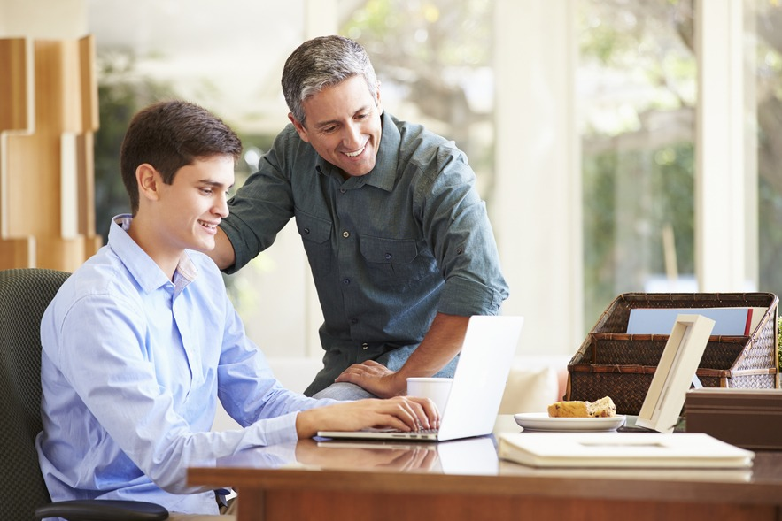 Father and teenage son looking at laptop